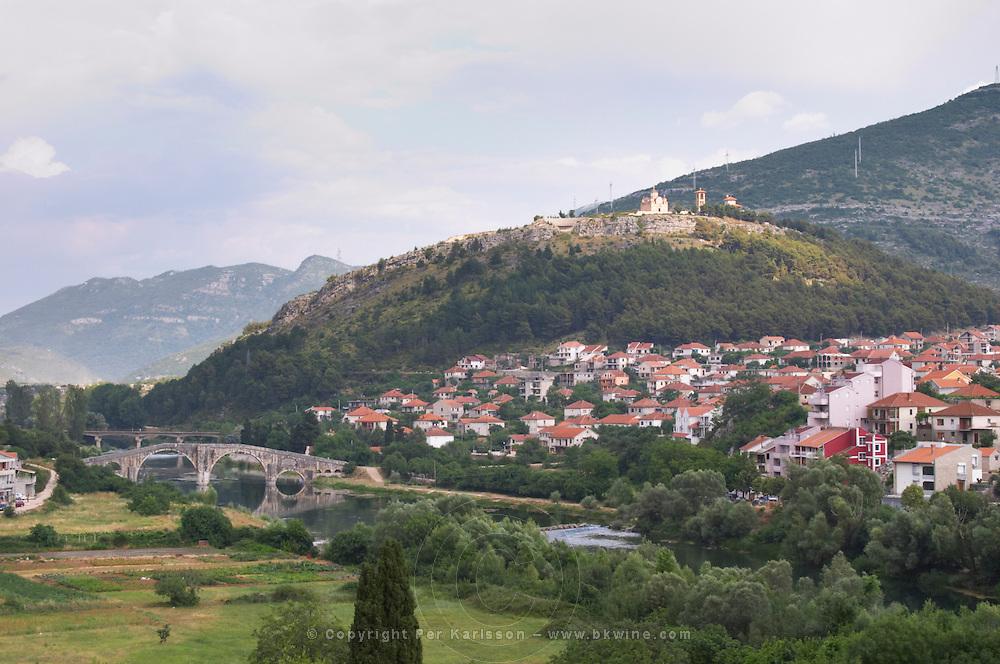 An old Roman stone bridge across the river Trebisnjica. Houses. The monastery Gracanica on the historic hill known as Crkvina against a mountain backdrop. Trebinje. Republika Srpska. Bosnia Herzegovina, Europe.