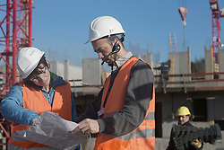 Two engineers looking at a blueprint at construction site, Freiburg Im Breisgau, Baden-Wuerttemberg, Germany