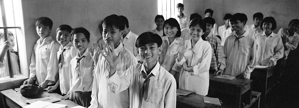 Boys smiling and standing in classroom