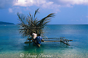 man paddling outrigger canoe is assisted by palm frond sail, Epi Island, Vanuatu, formerly known as New Hebrides<br /> South Pacific