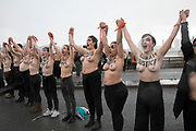In solidarity with International Womens Day, climate activists from Extinction Rebellion brave the cold of a rain squall to set up a topless road block on Waterloo Bridge in protest of the disproportionate effects climate change has on women and girls, especially during times of specific climate crisis on 8th March 2020 in London, England, United Kingdom. Extinction Rebellion is a climate change group started in 2018 and has gained a huge following of people committed to peaceful protests. These protests are highlighting that the government is not doing enough to avoid catastrophic climate change and to demand the government take radical action to save the planet.