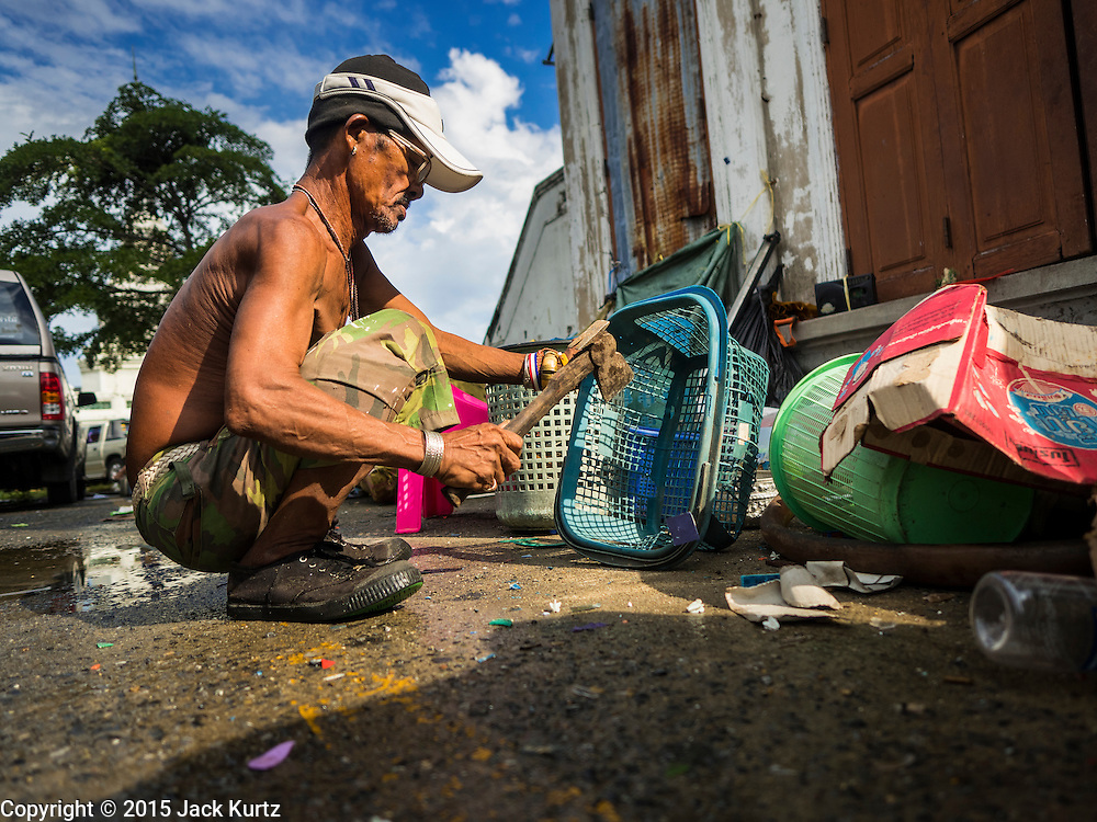 28 SEPTEMBER 2015 - BANGKOK, THAILAND: A man who lives in the Wat Kalayanamit neighborhood cuts up trash collected from homes destroyed in the neighborhood. Fifty-four homes around Wat Kalayanamit, a historic Buddhist temple on the Chao Phraya River in the Thonburi section of Bangkok, are being razed and the residents evicted to make way for new development at the temple. The abbot of the temple said he was evicting the residents, who have lived on the temple grounds for generations, because their homes are unsafe and because he wants to improve the temple grounds. The evictions are a part of a Bangkok trend, especially along the Chao Phraya River and BTS light rail lines. Low income people are being evicted from their long time homes to make way for urban renewal.    PHOTO BY JACK KURTZ