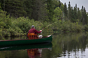 Brule River angler Matson Holbrook fly fishes from the bow of a 1895 Lucius guide canoe restored by Brule Guide Damian Wilmot.