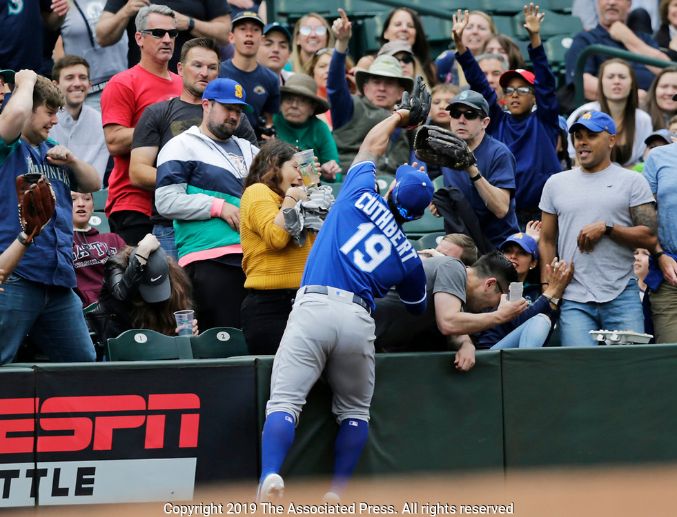 Kansas City Royals third baseman Cheslor Cuthbert reaches into the stands to catch a ball hit by Seattle Mariners' Kyle Seager for an out during the fourth inning of a baseball game, Wednesday, June 19, 2019, in Seattle. (AP Photo/John Froschauer)
