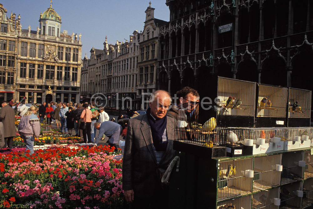 Bird fanciers admire caged tropical birds in the Grand Place Grote Markt, in Flemish bird market, Brussels, Belgium, on 24th June 1992, in Brussels, Belgium. In the cages are small birds from tropical countries, on sale every Sunday for those wanting avian company in their homes. The Brussels Grand Place hosts this bird market and the selection and prices are generally better than can be found in pet shops though the origins of these creatures are questionable. The Grand Place is Brussels' main city square, the focal point for colourful events throughout the year. Its Dutch-styled gabled guildhalls date from the 13th century and is now a UNESCO World Heritage Site.
