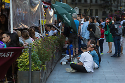 Fans in Leicester Square sit on the ground outside a restaurant to get a glimpse of the television. London, July 11 2018.