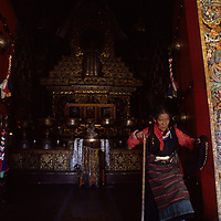 CHINA, TIBET. Tibetan Buddhist devotee leaves exits door of richly ornamented Tshomchen, the Main Assembly Hall at Palkhor Monastery in Gyantse.