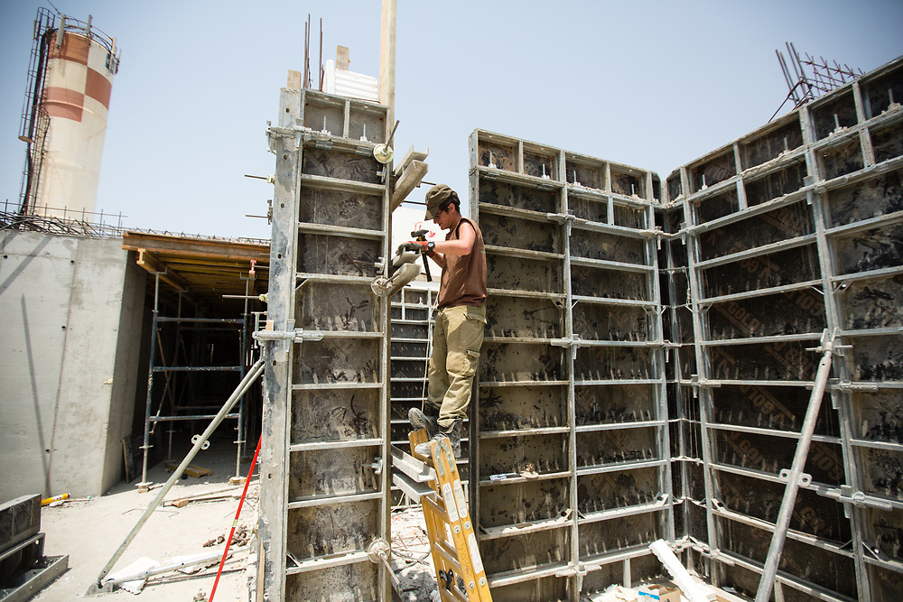 A Jewish Israeli laborer is seen during work at a construction site in the West Bank Jewish settlement of Yitzhar, south of the Palestinian West Bank city of Nablus, on August 5, 2015.