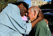 Client Michael Johnson of Hartford hugs friend Anthony Cymerys, known as Joe the barber in Hartford, Conn.
