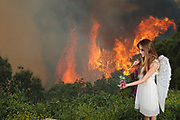 Fairy scatters fairy dust on a flower in a forest with a raging forest fire in the background