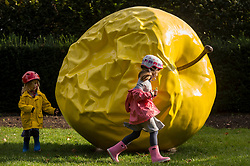 "© Licensed to London News Pictures. 29/09/2020. LONDON, UK. Iwana (3) (L) and sister Katrina (5) run round ""The Earth of Majesty, This Seat of Mars"" by Barnaby Barford which has been installed in Holland Park, west London, as part of Kensington and Chelsea Art Week's Public Art Trail.  These are other temporary landmarks have been installed across eight zones of the borough, connecting Royal Borough of Kensington and Chelsea provide a walking trail for the public to enjoy.  The event runs 1 October to 11 October 2020. (permission obtained)  Photo credit: Stephen Chung/LNP"