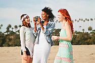 Three young women hanging out at the beach and taking photos.