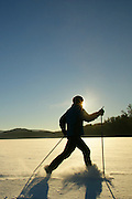 Man cross country skiing across a snowy field or lake.