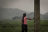 A young H'mong women contemplatively looks out over a green valley of Mong Xoa near Sa Pa, Lao Cai Province, Vietnam, Southeast Asia