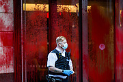 """A police officer observes """"one curzon"""" building following the action of Palestine Action activists that painted it in the red colour in London on Wednesday, June 9, 2021. (Photo by Marcin Nowak/VXP)"""