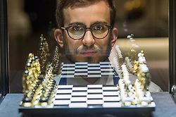 """© Licensed to London News Pictures. 25/10/2019. LONDON, UK. A technician poses next to """"a modern gilt-brass hardstone chess set"""" (Est. GBP6-8k).  Preview of """"GOLD: The Midas Touch"""" at Sotheby's in New Bond Street.  Artworks spanning six centuries dedicated to gold will be offered for sale on 29 October.  Photo credit: Stephen Chung/LNP"""