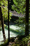 Hike across a bridge over beautiful Thunder Creek on the trail to Fourth of July Pass from Colonial Creek Campground, in Ross Lake National Recreation Area, in the North Cascades mountain range, Washington, USA. The best view is a mile short of the Pass, at Fourth of July Camp, 9 miles round trip with 2000 feet gain.