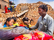 04 MARCH 2017 - KATHMANDU, NEPAL: A snack vendor does business in front of a stack of bricks being used to rebuild the shrines at Swayambhu Stupa. The stupa was badly damaged in the 2015 Nepal earthquake. Recovery seems to have barely begun nearly two years after the earthquake of 25 April 2015 that devastated Nepal. In some villages in the Kathmandu valley workers are working by hand to remove ruble and dig out destroyed buildings. About 9,000 people were killed and another 22,000 injured by the earthquake. The epicenter of the earthquake was east of the Gorka district.     PHOTO BY JACK KURTZ