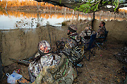 Duck hunters waiting in blind while hunting on a private watershed lake near Shamrock, Oklahoma