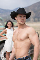 shirtless muscular cowboy with a girl looking at him from behind