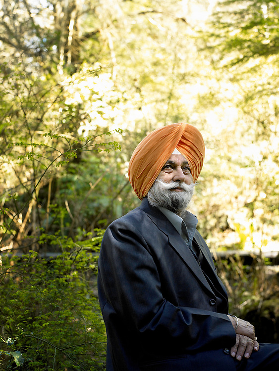 Portrait of older Sikh man sitting in the woods.