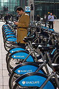 A city worker checks his blackberry cell phone whilst standing in the parking area for Barclays bikes in the plaza outside Canary Wharf station, Docklands, London, United Kingdom.