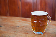 "Pint of ale in an old fashioned jug beer glass. Jug glasses are shaped more like a large mug with a handle. They are moulded with a grid pattern of thickened glass on the outside. Dimpled glasses are now rarer than the other types and are regarded as more traditional. This sort of glass is also known as a ""Handle"" or ""Jug"". They are popular with drinkers who prefer a traditional beer experience."