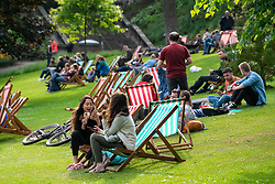 People relaxing on deckchairs in afternoon sun in Princes Street Gardens in Edinburgh , Scotland, UK