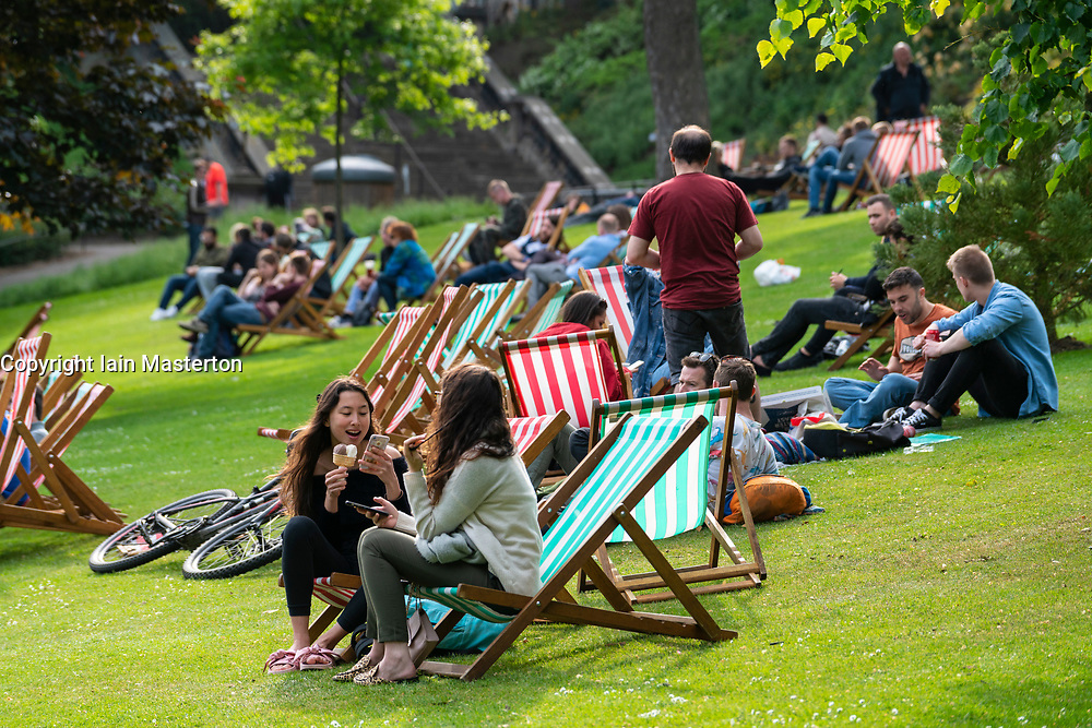 People relaxing on deckchairs in afternoon sun in Princes Street Gardens in Edinburgh , Scotland, UK