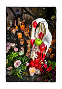 SHOT 2/10/20 9:25:48 AM - An offering of an apple at a  roadside capilla dedicated to Santa Muerte (Nuestra Señora de la Santa Muerte) near El Guamuchil, Mexico. Santa Muerte (Holy Death), is a female deity (or folk saint depending on school of thought) in Mexican folk religion, particularly Folk Catholicism, venerated primarily in Mexico and the Southwestern United States. A personification of death, she is associated with healing, protection, and safe delivery to the afterlife by her devotees. Despite condemnation by the Catholic Church her devotees have grown in numbers lately and many followers of Santa Muerte live on the margins of the law or outside it entirely. In the Mexican and U.S. press, the Santa Muerte cult is often associated with violence, criminality, and the illegal drug trade. Altars of Santa Muerte temples generally contain one or multiple images of the Lady, generally surrounded by any or all of the following: cigarettes, flowers, fruit, incense, water, alcoholic beverages, coins, candies and candles. Capillas are common along the roads and highways of Mexico which is heavily Catholic and are often dedicated to certain patron saints or to the memory of a loved one that has passed away. Often times they contain prayer candles, pictures, personal artifacts or notes. (Photo by Marc Piscotty / © 2020)