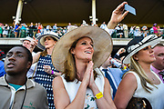 30174109A LOUISVILLE, KY. - MAY 2, 2015: Megan Weiland, middle, of Chicago, looks on as the horses take to the track before the running of the roses during the 141st running of the Kentucky Derby at Churchill Downs. This was Weiland's first Derby.<br /> <br /> William DeShazer for The New York Times