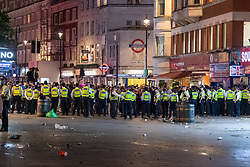 © Licensed to London News Pictures. 03/07/2021. London, UK. Police form a long cordon at the east end of Leicester Square in central London after football fans gathered to celebrate England's EURO2020 quarter-final football win against Ukraine, when police moved in to clear the crowd they clashed with fans and were pelted with bottles, police detained several people. Photo credit: Peter Manning/LNP