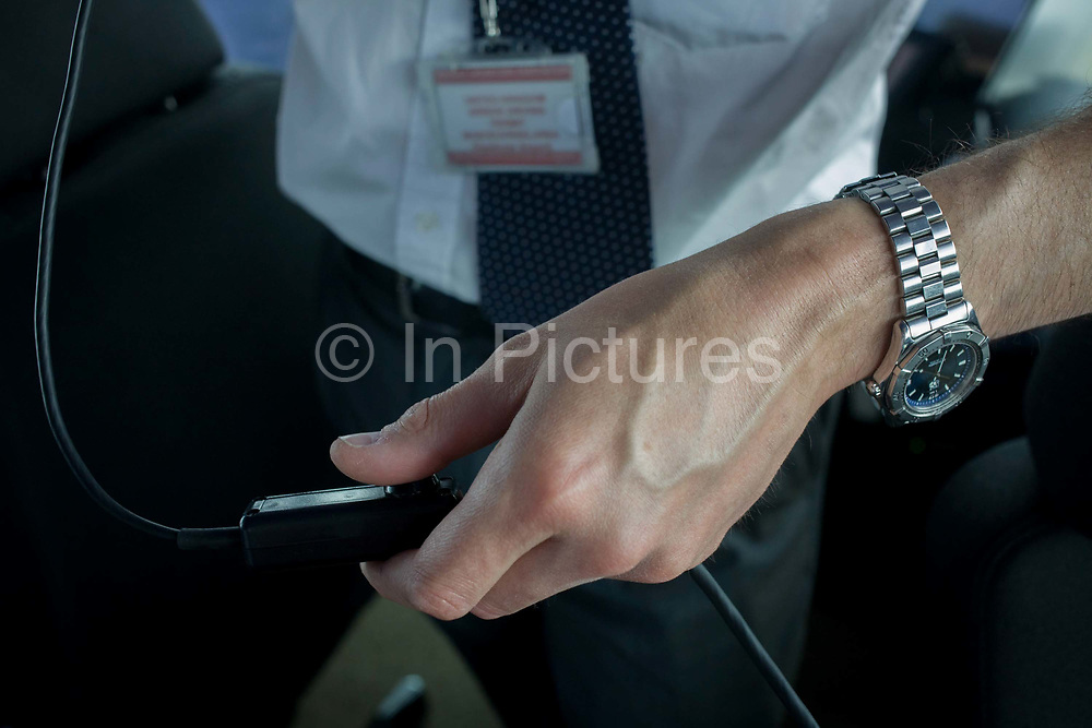 Detail of NATS air traffic controller's hand and radio trigger in control tower at Heathrow airport, London. A guiding hand and radio intercom control is seen in detail. Controlling aviation traffic on the ground and in the controlled airspace around London, the NATS controllers help safely guide up to 6,000 flights a day from the top of the 87 metre high tower, handling 1,350 aircraft movements a day into Heathrow.