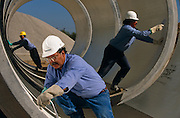 "Precast concrete pipes are prepared for distribution by a Mexican-born employees at Hanson Pipe & Products, Grand Prairie, Texas, USA. They are inspcting the inner-surfaces and tongue and groove seals of the horizontal pipes wearing obligatory hard hats and corporate blue shirts. Precast concrete is made from a reusable mold or ""form"" and cured in a controlled environment, then transported to the construction site and lifted into place. Used in the construction of commercial building components, bridges, manholes and retaining walls, these products are the strongest pipe available, designed and plant tested to resist any load required with a design life of 70-100 years. ..."