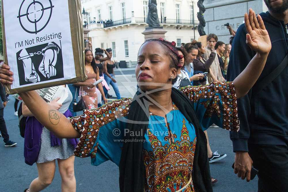 """London, July 8th 2016. Hundreds gather on London's Southbank before marching through the streets of London to Parliament Square, Downing Street and the BBC, in a Black Lives Matter protest in solidarity with Americans following the shooting dead of two black men, Philando Castile in Minnesota and Alton Sterling in Louisiana by police in the US. PICTURED: A woman marches with her hands up as the crowd chants """"Hands up! Don't shoot!""""."""