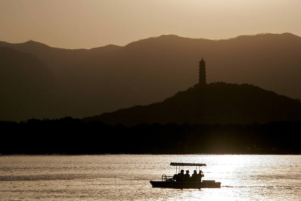 Visitors boat at sunset on the Kunming Lake at the Summer Palace.  The Summer Palace is in north west Beijing, China was built in the Jin Dynasty.  The Summer Palace is over 700 acres, 3/4 of which is the Kunming Lake.