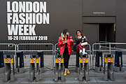 Two stylish women are eating their lunch while perched on empty Santander bike docks on the first day of London Fashion Week in the Strand, on 16th february 2018, in London, England.