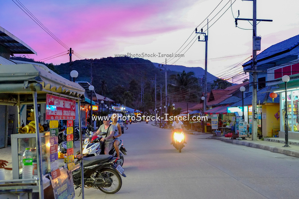Tourists on motorcycles on the one road of the village thong nai pan yai in Koh Phangan, Thailand