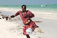 A Massai tribesman playing football on the beach.  Paje, Zanzibar, Tanzania