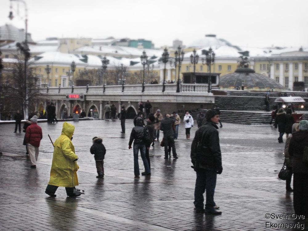 Ei dame kledd i gul regnfrakk feier gaten i Moskva. <br /> <br /> A woman dressed in a yellow raincoat is sweeping a street in Moscow.