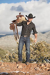 Hot cowboy with a saddle by a mountain range