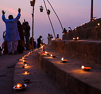 Varanasi, INDIA - CIRCA NOVEMBER 2018: People worshiping during a ceremony at the  Assi Ghat in Varanasi. The Aarti is a powerful and uplifting spiritual ritual that takes place every evening at dusk. Varanasi is the spiritual capital of India, the holiest of the seven sacred cities and with that many rituals and offerings are performed daily by priests and hindus.