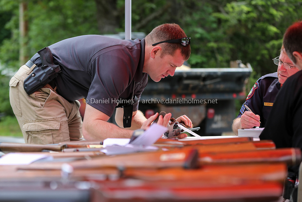 (6/3/17, NATICK, MA) Natick police officer Eric Bazigian looks for a serial number on a gun during the gun buyback at the Hartford Street Presbyterian Church in Natick on Saturday. [Daily News and Wicked Local Photo/Dan Holmes]