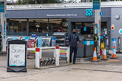 Licensed to London News Pictures. 25/09/2021. London, UK. An attendant stands next to large signs of 'no fuel' at a Co-op petrol station on the A3 in Roehampton, south-west London this morning as desperate motorists stop to fill up, only to discover the garage has run out of fuel. Yesterday, Large queues formed at petrol stations across London with many running out of fuel as oil giants struggle to maintain deliveries due to the lack of HGV drivers. Photo credit: Alex Lentati/LNP