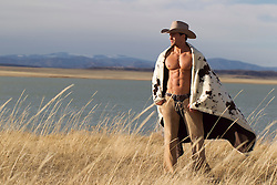 very sexy cowboy without a shirt wearing a blanket by a lake in New Mexico