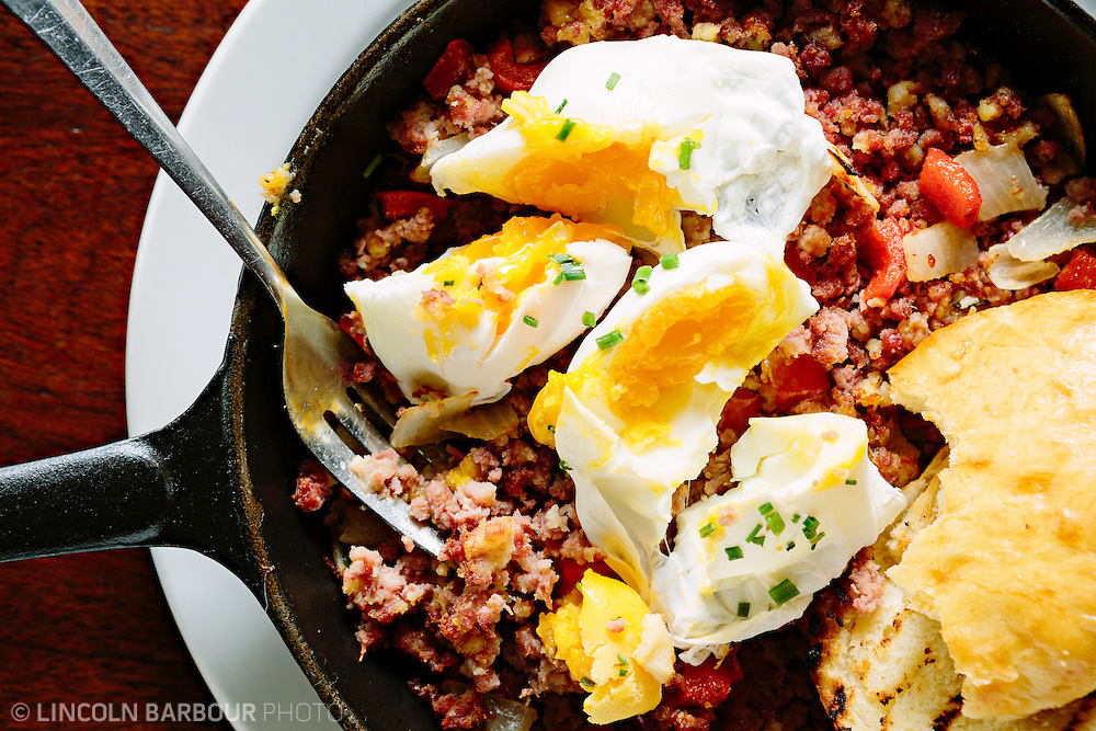 Poached eggs broken over hash with a some toasted bread all served in a cast iron skillet. A rustic looking display shot from the top down.