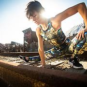 Female athlete stretching on train tracks next to a salt mine in San Diego, CA.