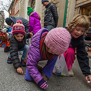 From left, Gwyn Stevens, Chandler Sharp and Laurel Schmalzer pick up candy thrown by parade participants during the Charleston Christmas parade in Charleston, W.Va., on Saturday, December 08, 2018.