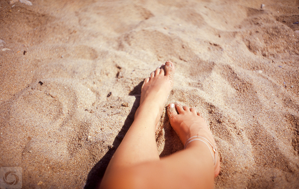 A film photograph from the first person POV of toes in the sand at the beach at Dories Cove of Block Island, Rhode Island