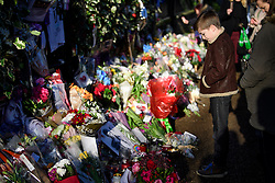 © Licensed to London News Pictures. 28/12/2016. London, UK. A young boy looks at tributes, left outside the London home of singer and musician George Michael, in Highgate, North London. Pop superstar George Michael died on Christmas day at his Oxfordshire home on the River Thames aged 53. Photo credit: Ben Cawthra/LNP